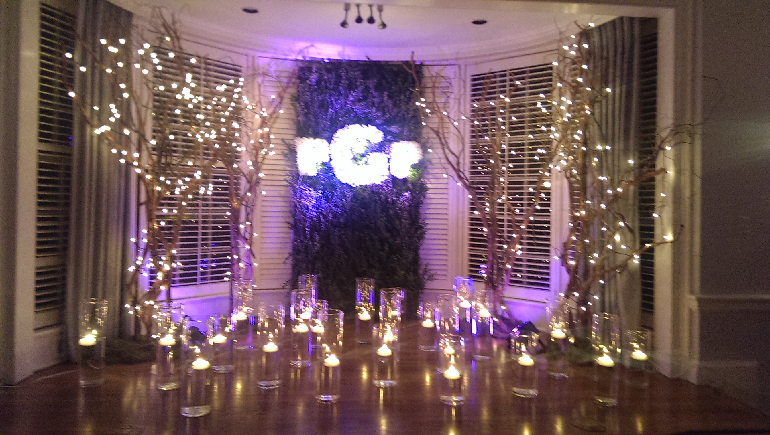 Fairytale reception gilded bow the brides monogram in lush greenery surrounded by beautiful tea lights in vases of water and reviewsmspy